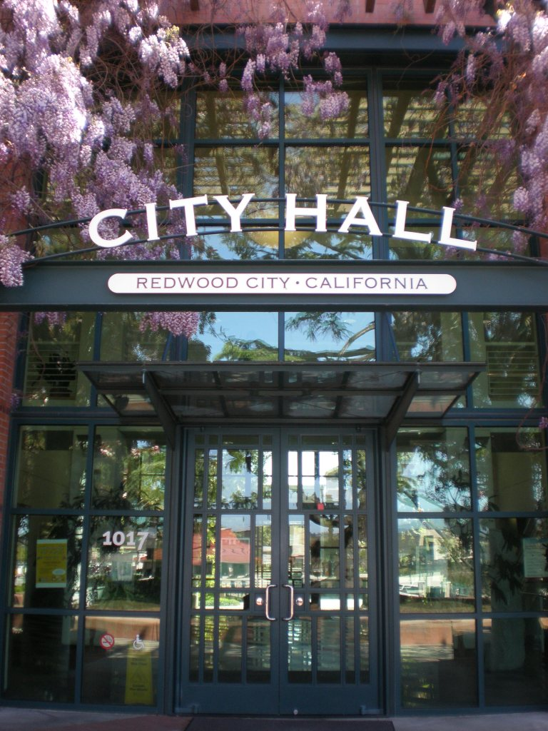 Front doors and sign, surrounded by pink cherry blossoms, of city hall in Redwood City, California.